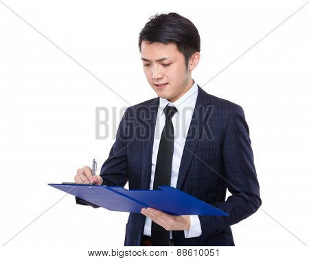 Businessman jot note on clipboard