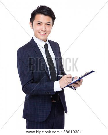 Businessman write on the clipboard