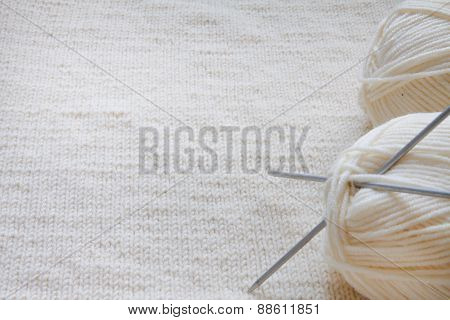 Ball of yarn and knitting on a wool background