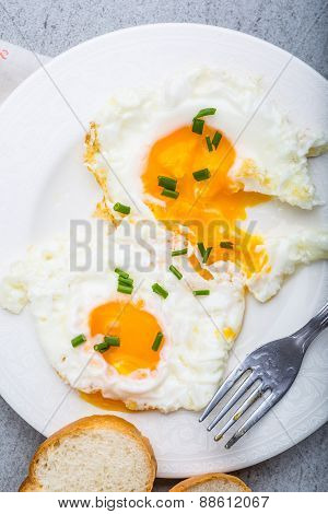 Two Fried Eggs With Chives On White Plate