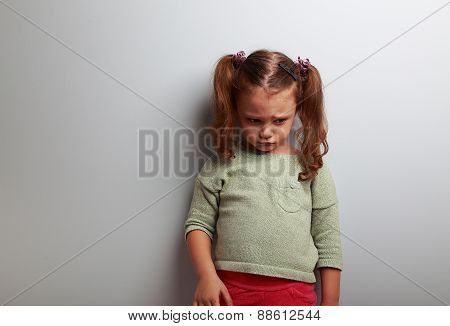 Unhappy Abandoned Kid Girl Looking Down On Blue Background