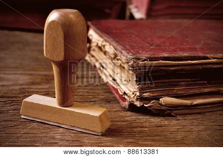 closeup of a rubber stamp and a worn-out old book, on a rustic wooden table