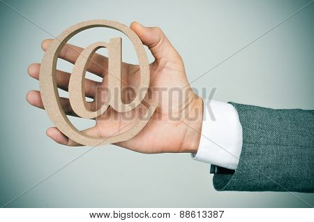 closeup of the hand of a young caucasian businessman in a grey suit showing a wooden at sign