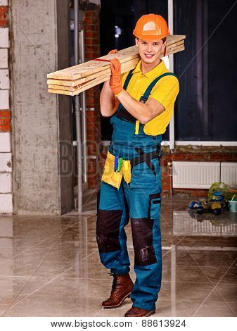 Man in builder uniform carry boards indoor. Yellow t-shirt.