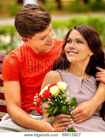 Couple with flower at park on bench. Outdoor. Man hugging girl.