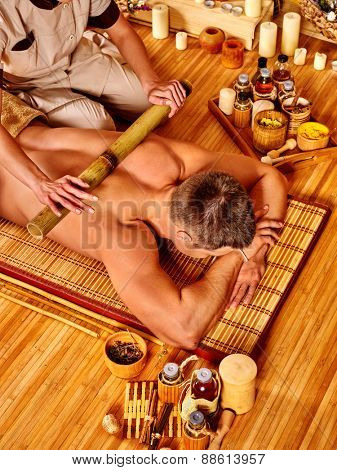 Man getting bamboo massage. Female therapist. Stick in hands.