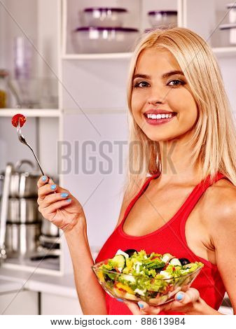 Happy woman eating salad at kitchen. Red t-shirt.