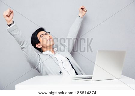 Happiness businessman sitting at the table with laptop over gray background