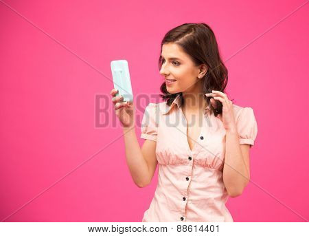 Happy woman holding mirror over pink background