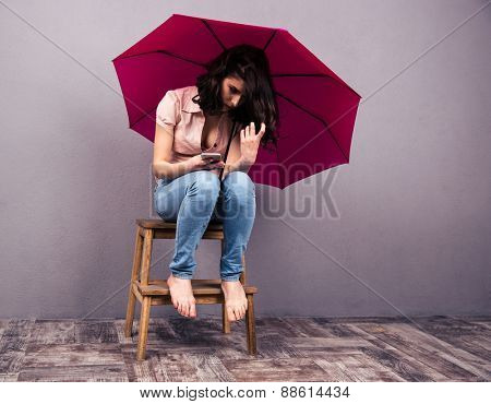 Young woman sitting on the chair with smartphone and pink umbrella. Wearing in shirt and jeans.