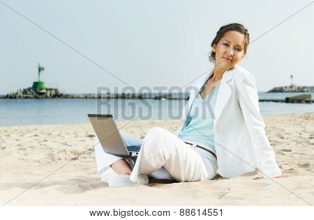Businesswoman With Laptop Sitting On A Beach