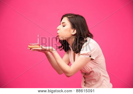 Side view portrait of a young woman holding donut and blowing on candle over pink background