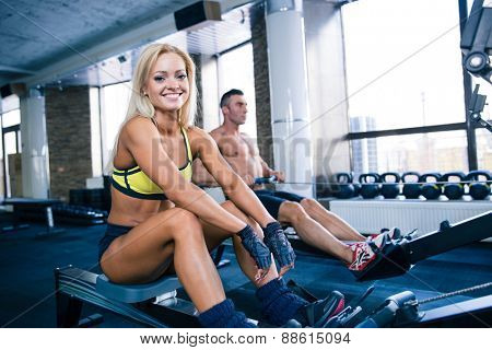 Happy woman sitting on training simulator and looking at camera with man on background