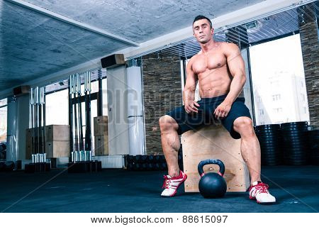 Muscular handsome man sitting on fit box in gym and looking at camera