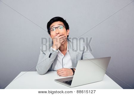 Amazed businessman sitting at the table with laptop over gray background and looking at camera. Covering his mouth
