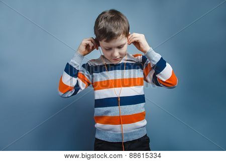 European-looking boy of ten years listening to music with headph