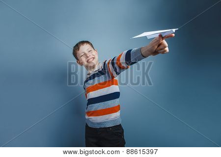 European-looking boy of ten years playing paper airplane on a gr