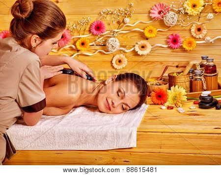 White woman getting  massage in wooden spa.