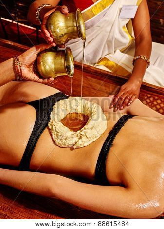 Young woman having stomach Ayurveda spa treatment. Treatment of lumbar.