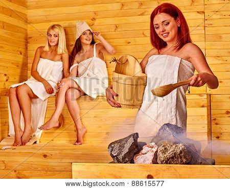 Women pouring water on rock in sauna. Three people.