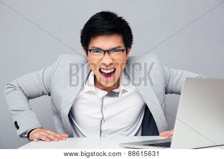 Angry young man sitting at the table with laptop and screaming on camera over gray background