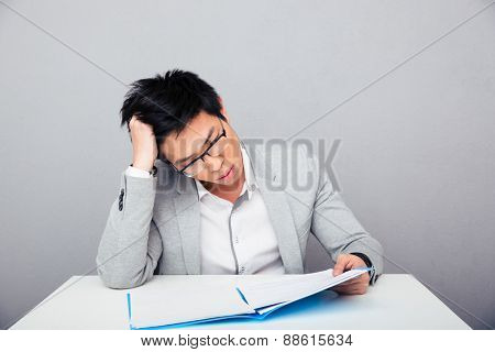 Businessman sitting at the table and reading papers in office