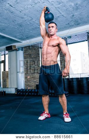 Full length portrait of a handsome bodybuilder workout with kettle ball in crossfit gym