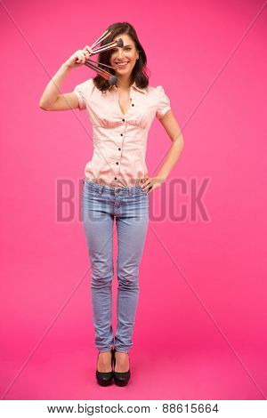 Full length portrait of a smiling woman holding brushes over pink background