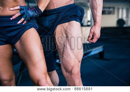 Closeup image of a strong woman and muscular man posing at gym