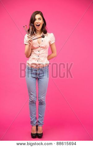 Full length portrait of a surprised young woman holding brushes over pink background and looking at camera