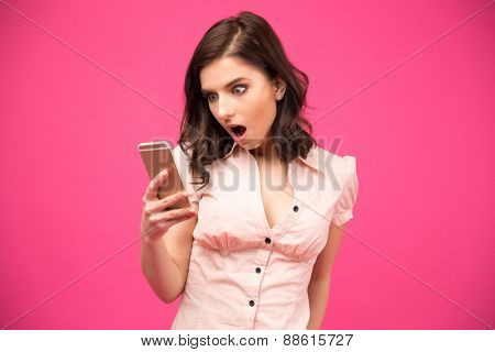 Surprised woman using smartphone over pink background. Wearing in shirt