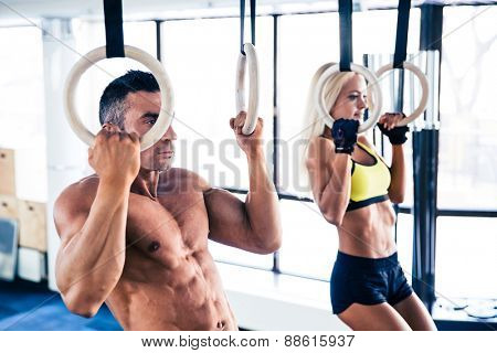 Handsome muscular man and beautiful woman workout on fitness rings in crossfit gym