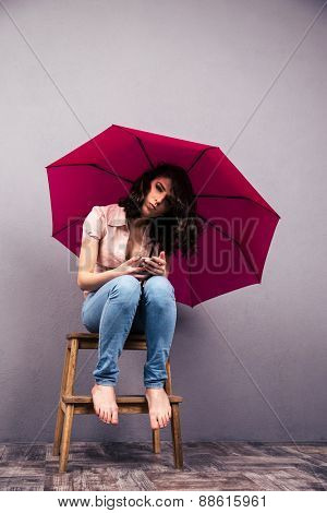 Young woman sitting on the chair with pink umbrella at studio. Looking at camera
