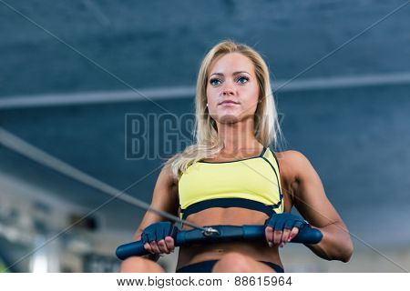 Woman working out on training simulator at gym