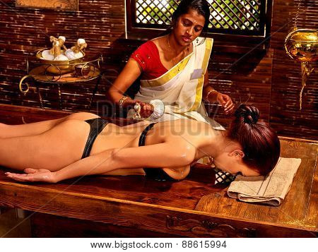Woman having ayurvedic massage with pouch of rice. Two people.