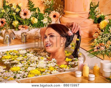 Woman relaxing at water flowers spa.