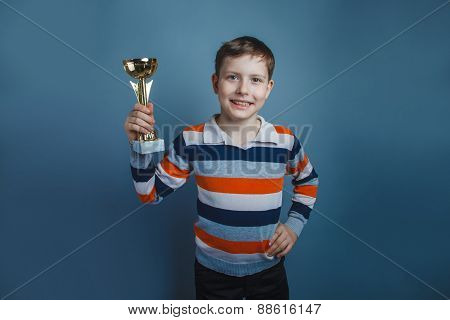 European-looking boy of ten years holding a cup award on a gray