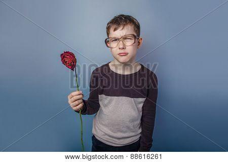 European-looking boy of ten years in glasses holding a dry flowe
