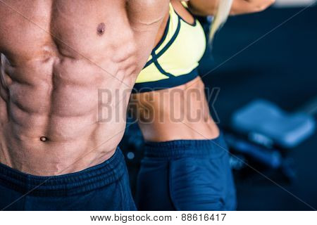 Closeup image of a muscular man's and strong woman's torso