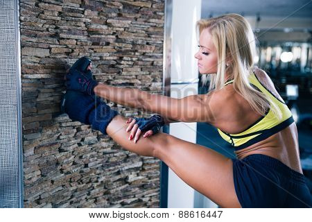 Sports beautiful woman stretching leg at gym