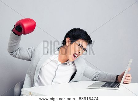 Angry young businessman sitting at the table and reading to hit the laptop over gray background
