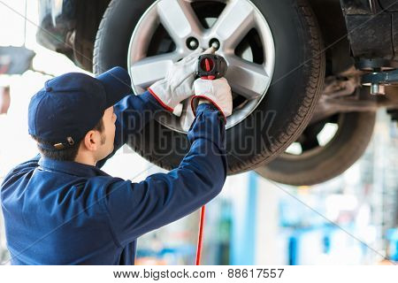 Mechanician changing car wheel in auto repair shop