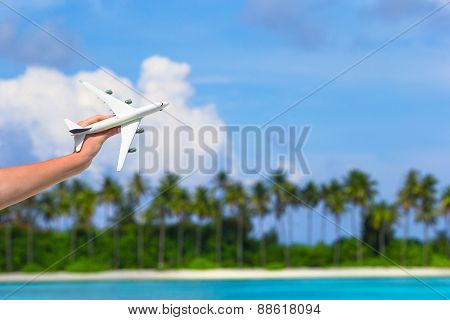 Small white toy airplane on tropical beach in human hand