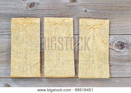 Three New Burlap Bags On Aged Wood