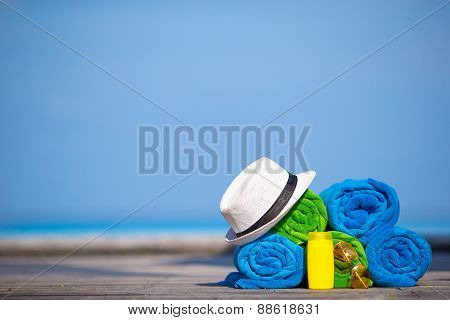 Beach and summer vacation accessories concept - close-up of colorful towels, hat and sunscreen