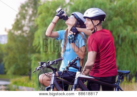 Sport And Cycling Concept: Young Caucasian Cyclist Resting Together Outdoors. Having Water Break And