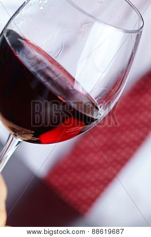 man handing glass of wine