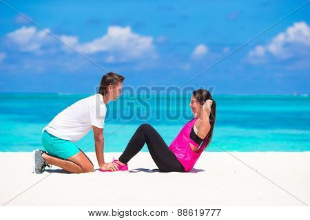 Young couple do abdominal crunches on white beach during vacation