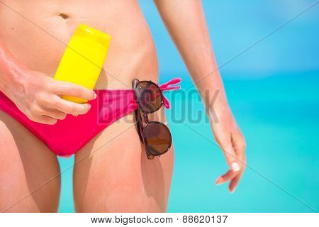 Beautiful young woman holding a sunscreen at  tropical beach