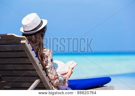 Young woman reading book on summer vacation at white beach